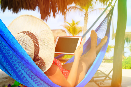 young woman relaxing in hammockwith touch pad at the sea beach photo