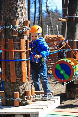 little boy climbing in adventure activity park with helmet and safety equipment photo