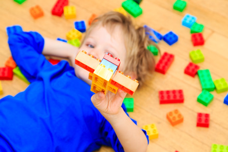 early learning: child playing with colorful plastic blocks indoor, early learning Foto de archivo