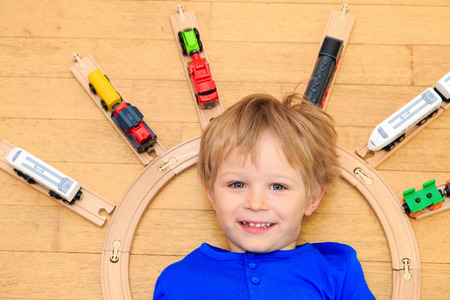 early learning: child playing with trains indoor, early learning Foto de archivo