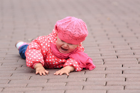 crying little girl fall off on sidewalk, kids safety Stock Photo