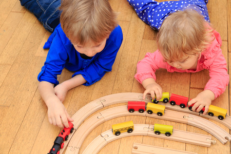 kinder: ni�os jugando con el ferrocarril y trenes cubierta, el aprendizaje y la guarder�a Foto de archivo