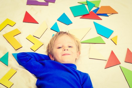 early learning: happy little boy with puzzle toys on white, early learning