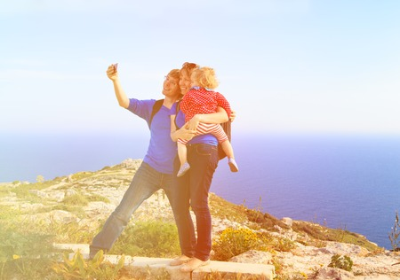 filming point of view: family with little daughter making selfie while hiking in summer mountains Stock Photo