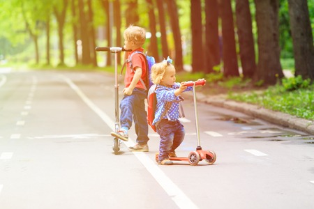 sister: two kids boy and girl-brother and sister- riding scooters in the city