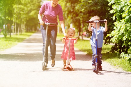 mother with kids riding scooters in summer, family sport