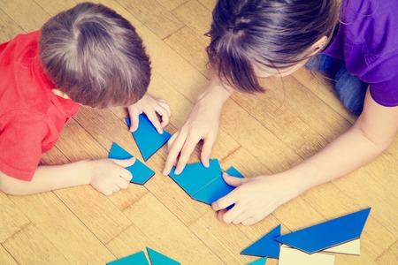 early learning: manos del profesor y el ni�o jugando con formas geom�tricas, el aprendizaje temprano Foto de archivo