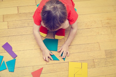game block: little boy playing with puzzle, early education concept