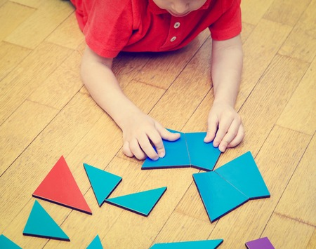 early education: little boy playing with puzzle, early education concept