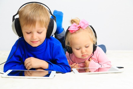 little boy and toddler girl with headset using touch pad, early education and learning