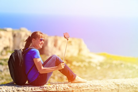 travel destination: tourist making selfie photo with stick on mountains travel