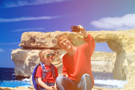 making hole: father and son making selfie photo against Azure Window on Gozo island, family travel
