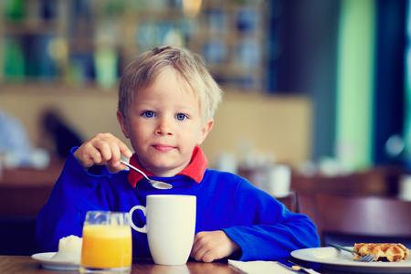 eating breakfast: happy little boy eating breakfast in cafe