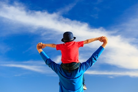 happy father and little son on shoulders play on sky Foto de archivo