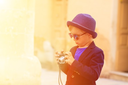 outside shooting: smart little boy taking photos while travel in Europe, Malta