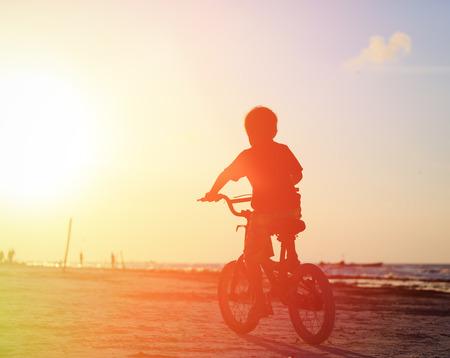 silueta ciclista: niño montando en bicicleta en la playa de la puesta del sol