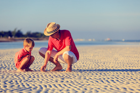 30s adult: father and son collecting seashells on summer tropical beach Stock Photo