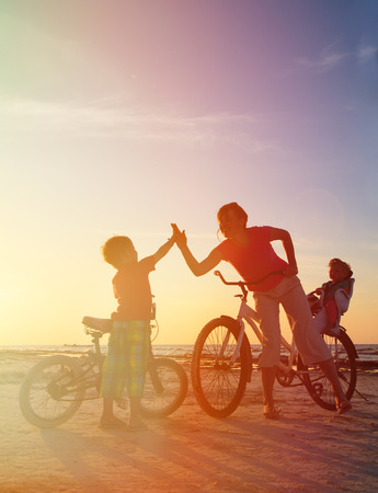 active people: Biker family silhouette at sunset, mother with two kids on bikes