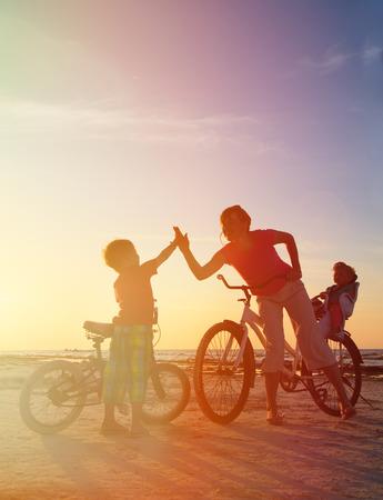 Silueta de la familia del motorista en la puesta del sol, madre de dos niños en bicicleta