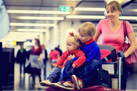 airport: mother with two kids travel in the airport, family travel Stock Photo