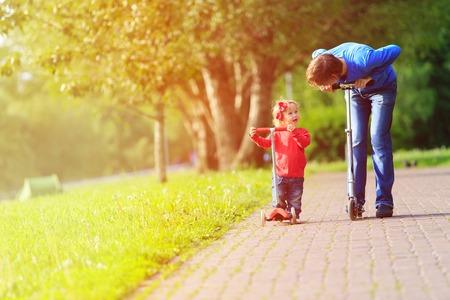 preguntando: Padre y pequeña hija montando motos, deporte familiar
