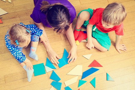 infant hand: teacher and kids playing with geometric shapes, early learning