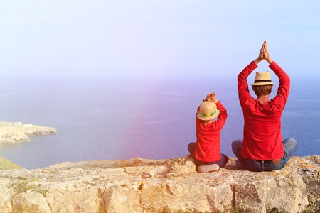 father's: father and little son doing yoga in mountains at the sea Stock Photo