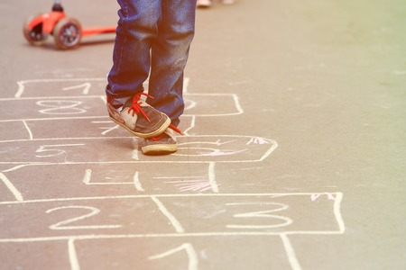 hopscotch: little boy playing hopscotch on playground outdoors