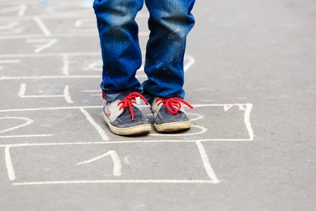 urban road: little boy playing hopscotch on playground outdoors