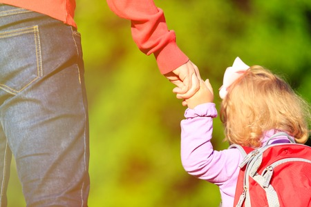 children hands: Mother holding hand of little daughter with backpack outdoors Stock Photo