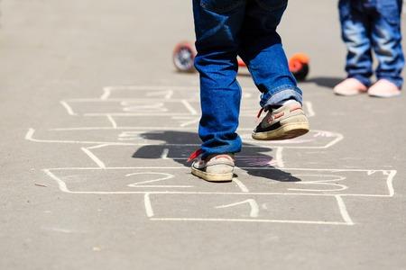 Enfants jouant à la marelle sur aire de jeux en plein air, activités de plein air pour enfants Banque d'images - 41048904