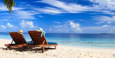 silla: Dos sillas de playa en la playa de arena tropical Foto de archivo