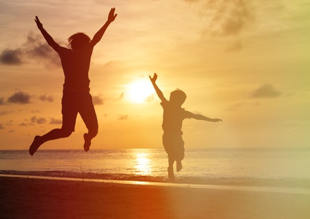 vader en zoon springen bij zonsondergang strand, gelukkig gezin