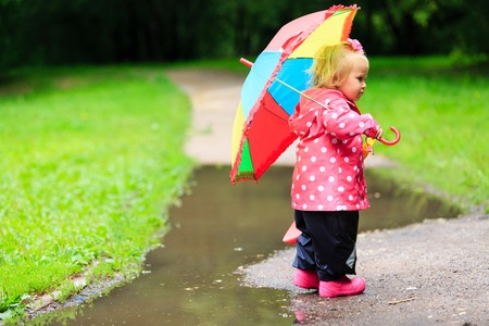 autumn rain: cute little girl with umbrella in raincoat and boots outdoor