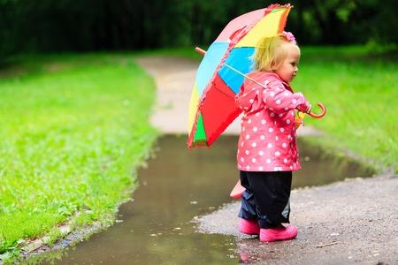 rain boots: ni�a linda con el paraguas en impermeable y botas al aire libre