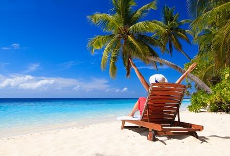 glückliche junge Frau sitzt auf Liegestuhl am tropischen Strand Standard-Bild