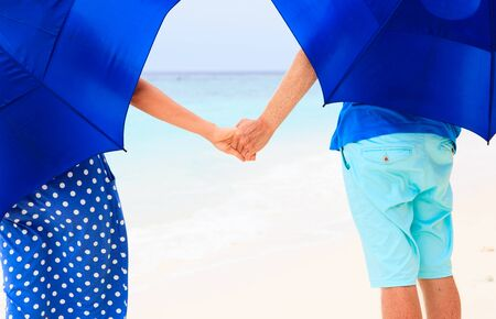 couple in rain: young romantic couple holding hands on rainy day beach