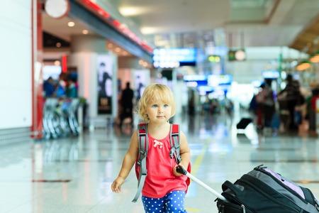 viajes: niña con maleta de viaje en el aeropuerto, viajan niños