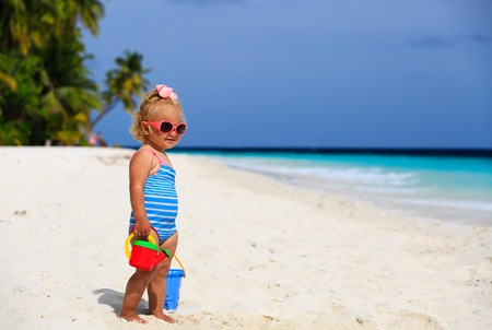 sand toys: cute little girl playing with sand on tropical beach Stock Photo