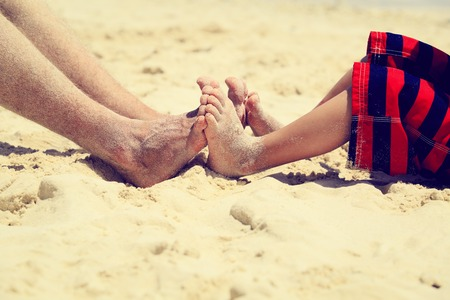 by feet: father and son feet on summer beach, family relax