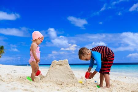 sandcastle: little boy and toddler girl building sandcastle on summer beach