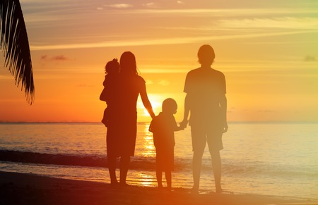 happy family: happy family with two kids on sunset tropical beach Stock Photo