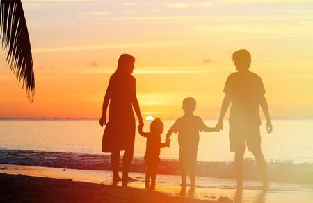 happy family with two kids on sunset tropical beach Imagens