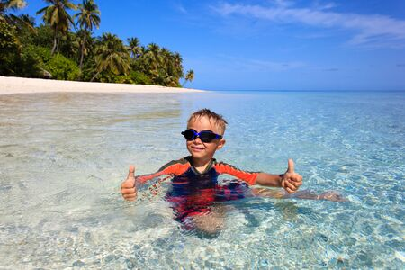 splash of water: happy little boy swimming on tropical beach vacation