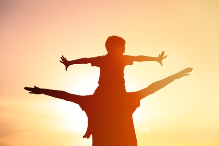 mosca: father and little son having fun at sunset sky