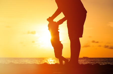 father's: silhouettes of father and little daughter walking on beach at sunset