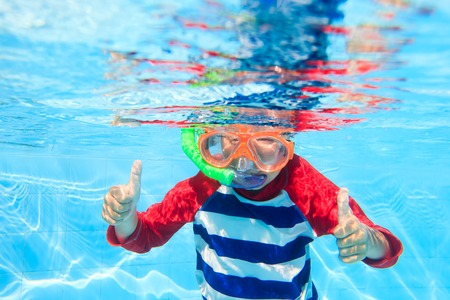 underwater sport: cute happy little boy swimming underwater with thumbs up
