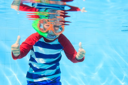 little boy swimming: cute happy little boy swimming underwater with thumbs up