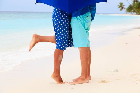 love in rain: legs of kissing young couple on rainly day at tropical beach
