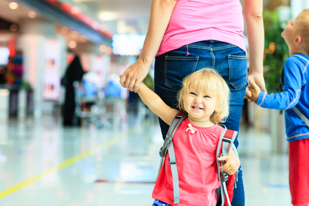 adult child: mother and two kids walking in the airport, family travel